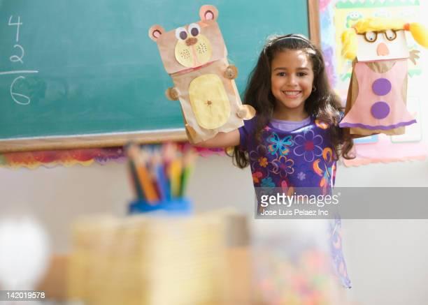 Hispanic girl holding sack puppets in classroom