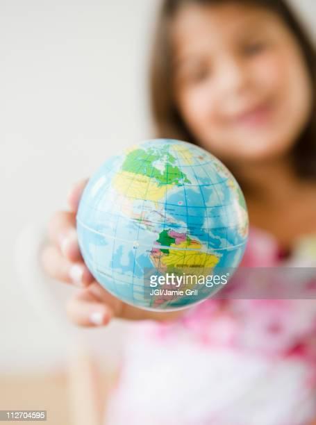 Hispanic girl holding small globe