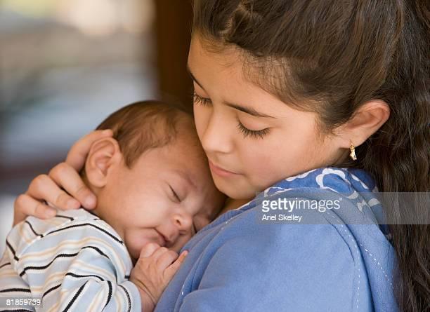 Hispanic girl hugging baby sibling