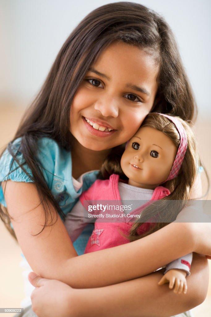 Hispanic girl hugging doll