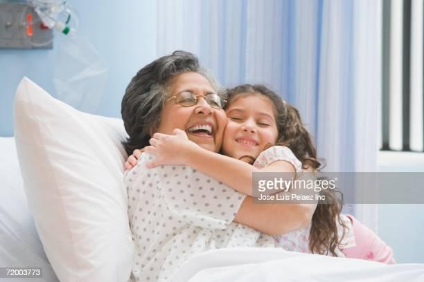 Hispanic girl hugging grandmother in hospital bed