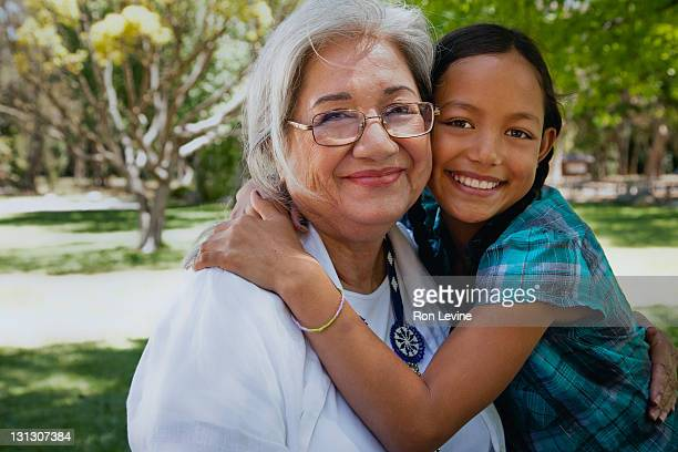 Hispanic girl hugging her grandmother, portrait
