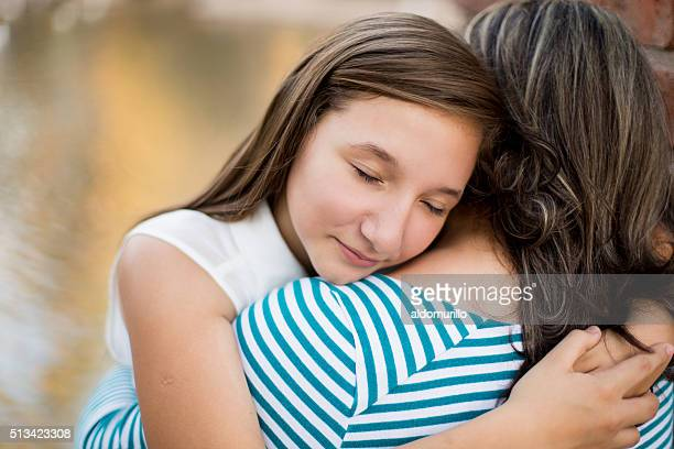 Hispanic girl hugging her mother