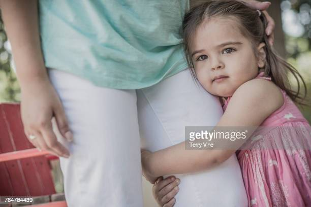 Hispanic girl hugging leg of mother