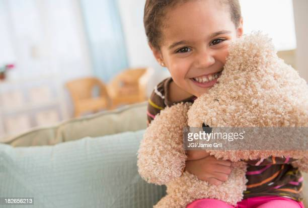 Hispanic girl hugging teddy bear on sofa