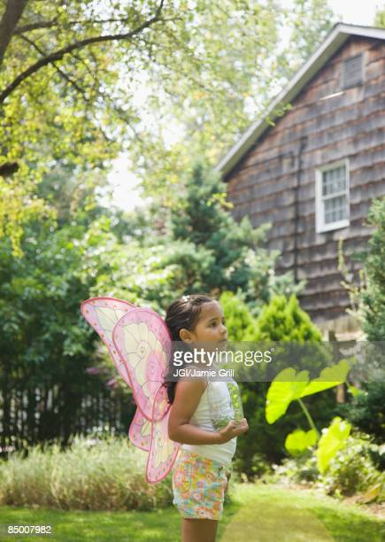 Hispanic girl in butterfly costume with jar