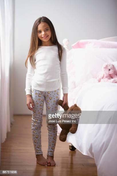Hispanic girl in pajamas holding teddy bear