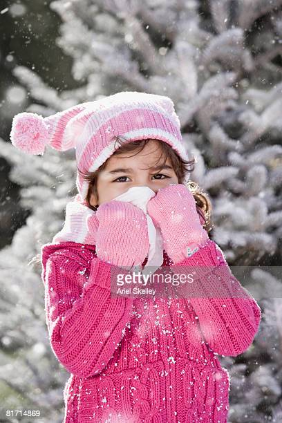 Hispanic girl in snow blowing nose