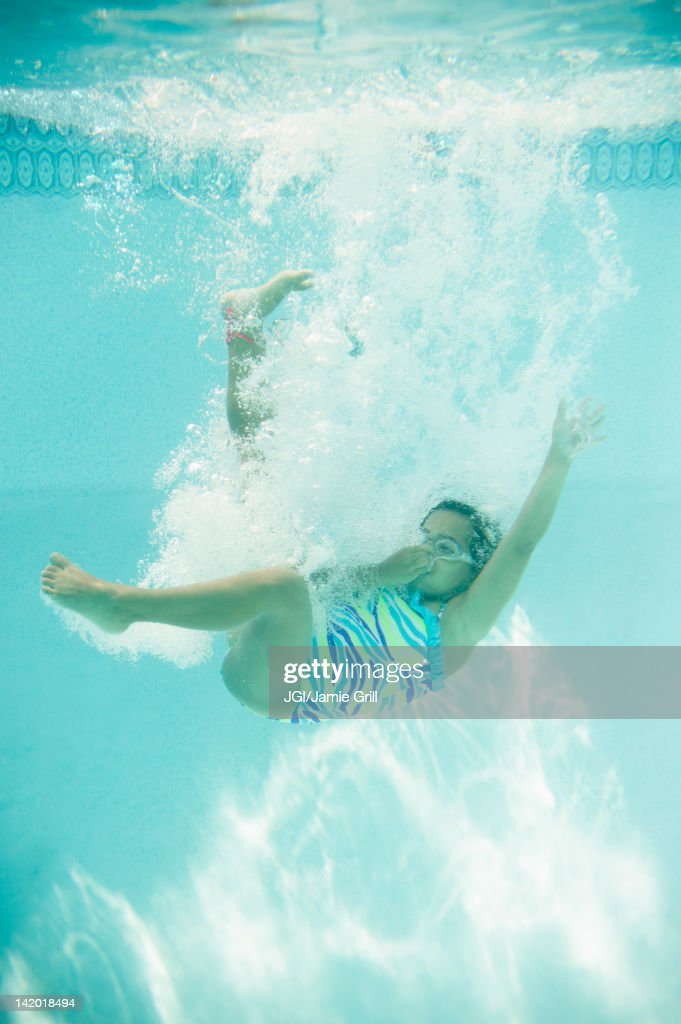 Hispanic Girl Jumping Into Swimming Pool Stock Photo Getty Images