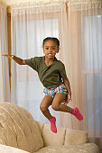 Hispanic girl jumping on a couch