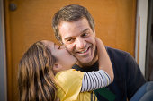 Hispanic girl kissing father's cheek