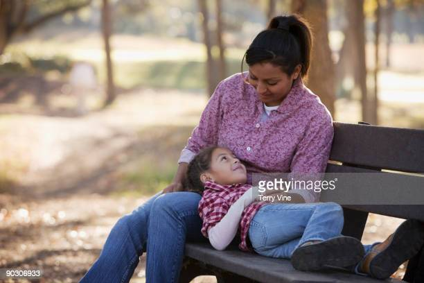 Hispanic girl laying in mother's lap on park bench