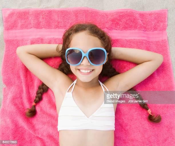 Hispanic girl laying on beach in bikini and sunglasses