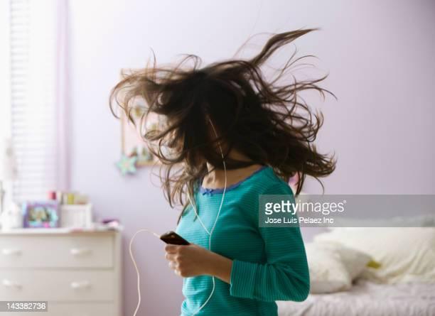 Hispanic girl listening to mp3 player and dancing