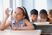 Hispanic girl looking at spider specimen in plastic