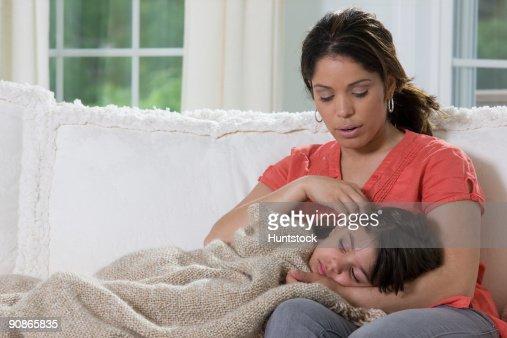 Hispanic girl lying on her mother's lap : Foto de stock