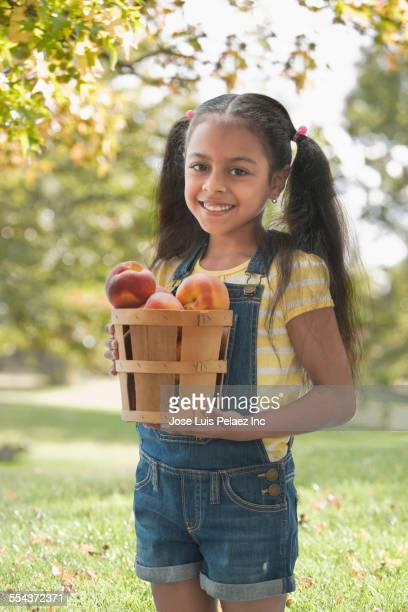 Hispanic girl picking apples in orchard