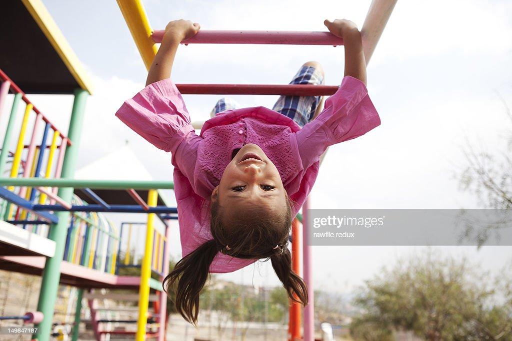 Hispanic girl playing in the monkey bars. : Stock Photo
