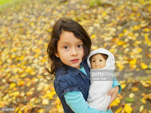 Hispanic girl playing outdoors with baby doll