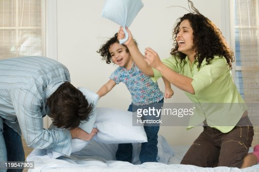 Hispanic girl playing pillow fight with her parents : Foto de stock
