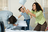 Hispanic girl playing pillow fight with her parents