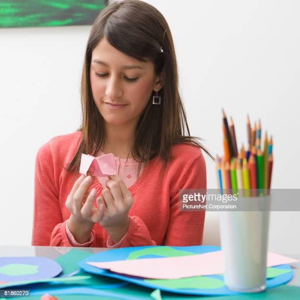 Hispanic girl playing with paper fortune teller