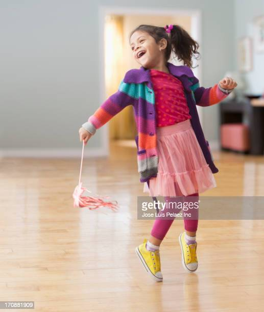 Hispanic girl playing with streamers
