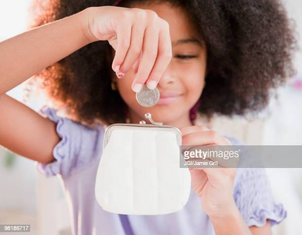 Hispanic girl putting coin into purse