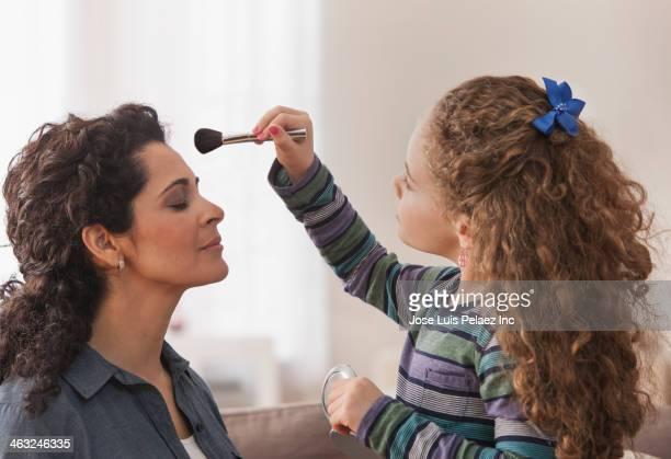 Hispanic girl putting makeup on mother