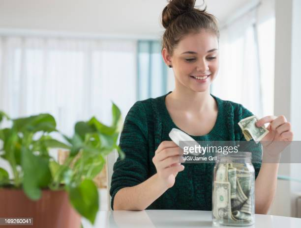 Hispanic girl putting money in savings jar
