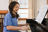 Hispanic girl reading a music sheet and playing a piano