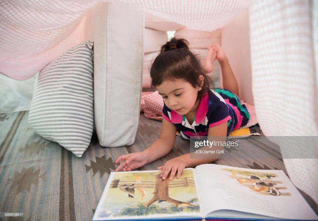 Hispanic girl reading in fort