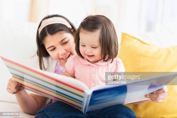 Hispanic girl reading to toddler sister in living room