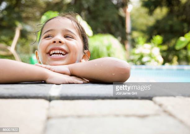 Hispanic girl resting at poolside