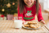 Hispanic girl setting out milk and cookies for Santa