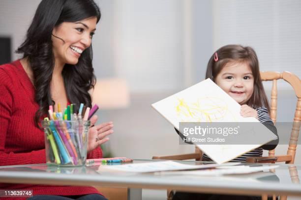 Hispanic girl showing drawing to mother