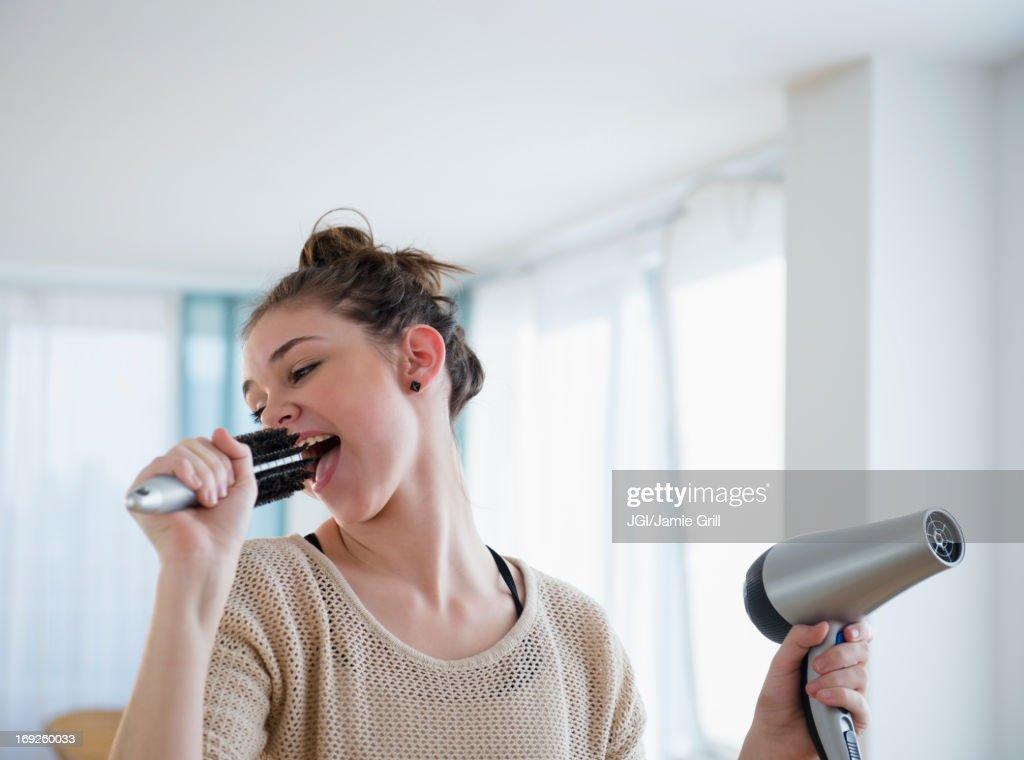 Hispanic girl singing into hairbrush : Stock Photo