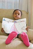 Hispanic girl sitting showing a drawing