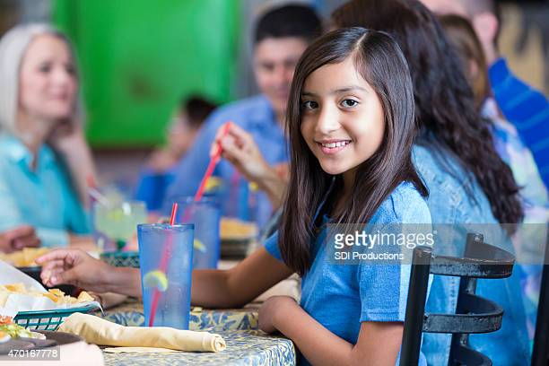 Hispanic girl smiling during meal with large family at restaurant