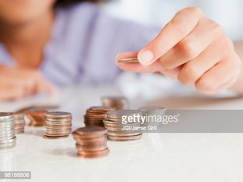 Hispanic girl stacking coins : Foto de stock