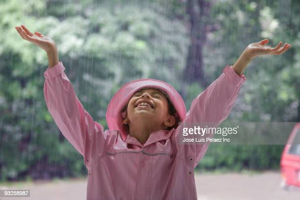 Hispanic girl standing in rain with arms raised