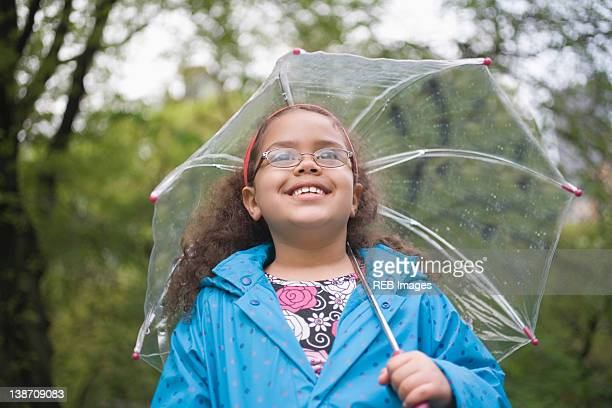 Hispanic girl standing in rain with umbrella