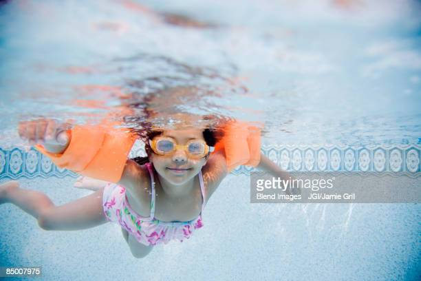 Hispanic girl swimming underwater in pool