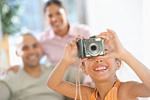 Hispanic girl taking a picture with a digital camera with her parents in the background