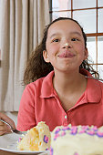 Hispanic girl trying to lick the cake icing on her nose