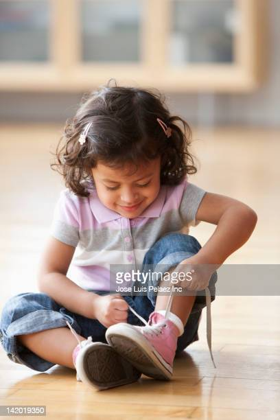 Hispanic girl tying her shoes