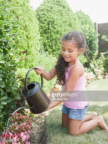 Hispanic girl watering flowers