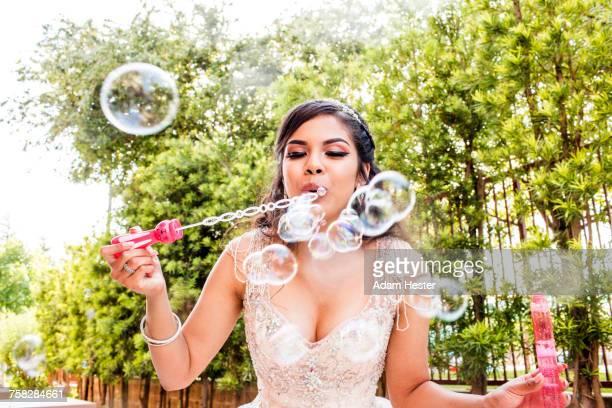 Hispanic girl wearing gown blowing bubbles