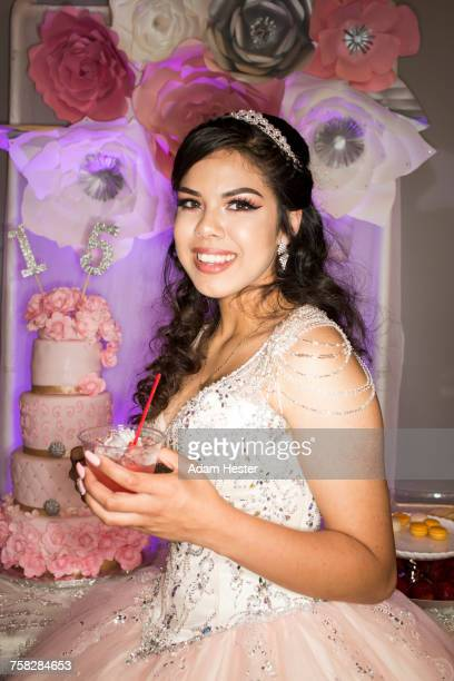 Hispanic girl wearing gown drinking beverage with straw