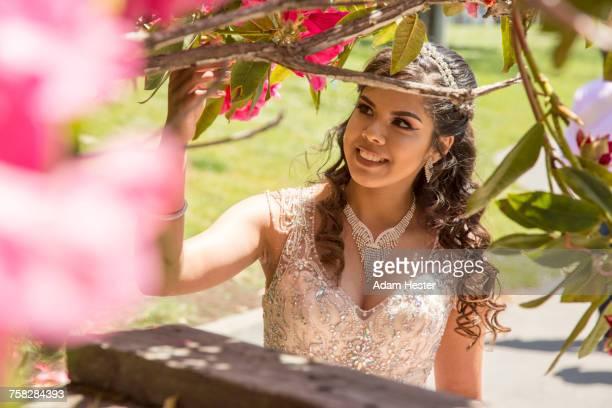 Hispanic girl wearing gown examining tree branch